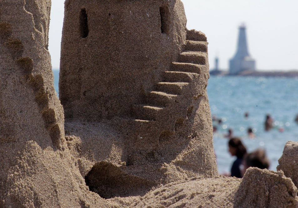Sandcastle with lighthouse in the background