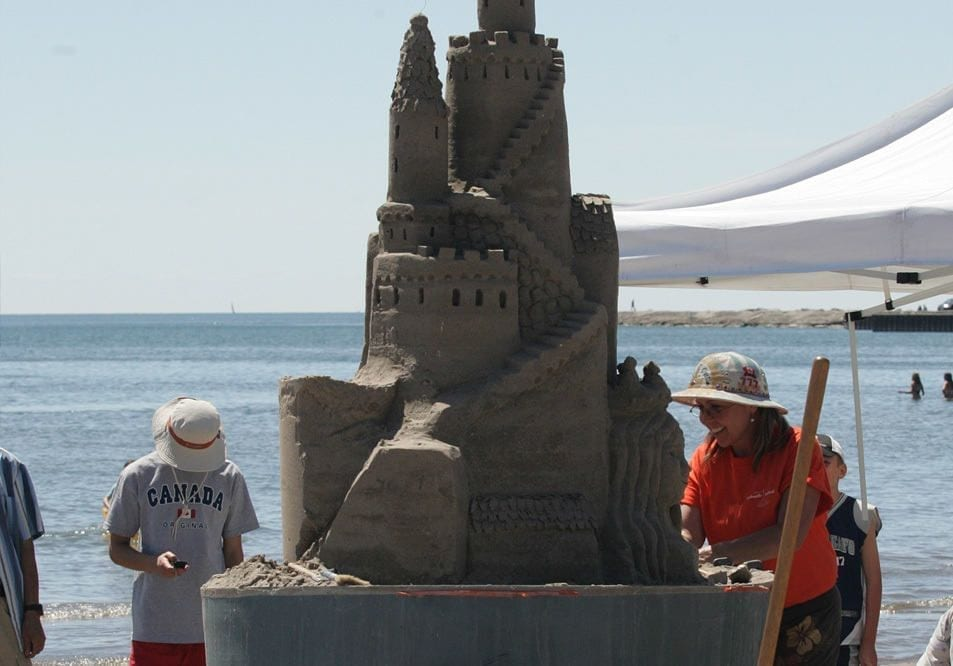 Visitors looking at giant sandcastles