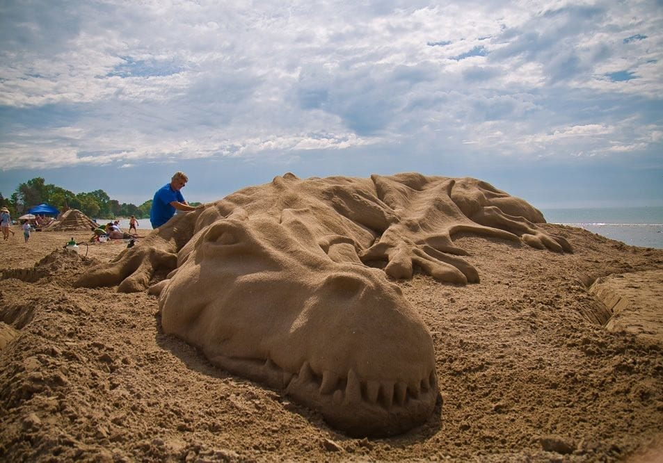 Artist working on a giant dragon made out of sand