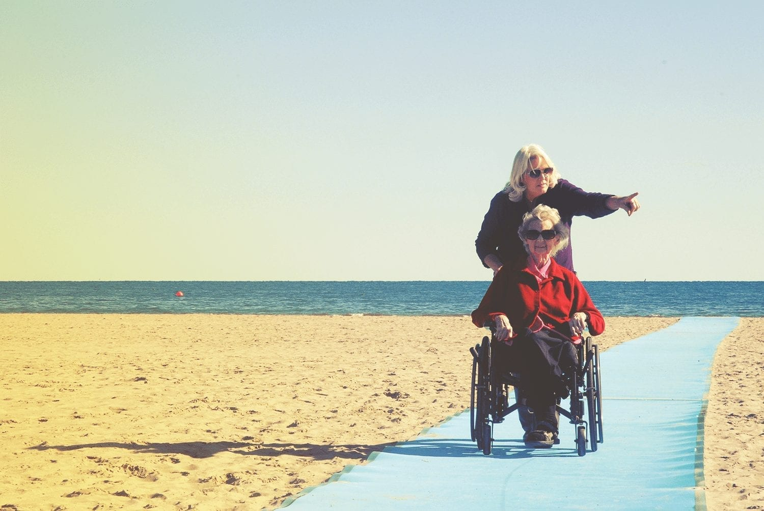 Daughter pushing elederly mother in wheelchair on the accessible path at Cobourg beach